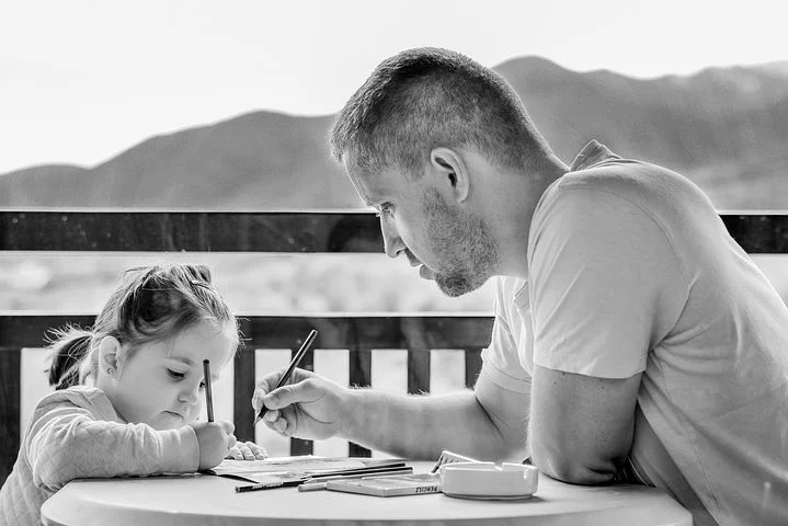 father and child drawing together