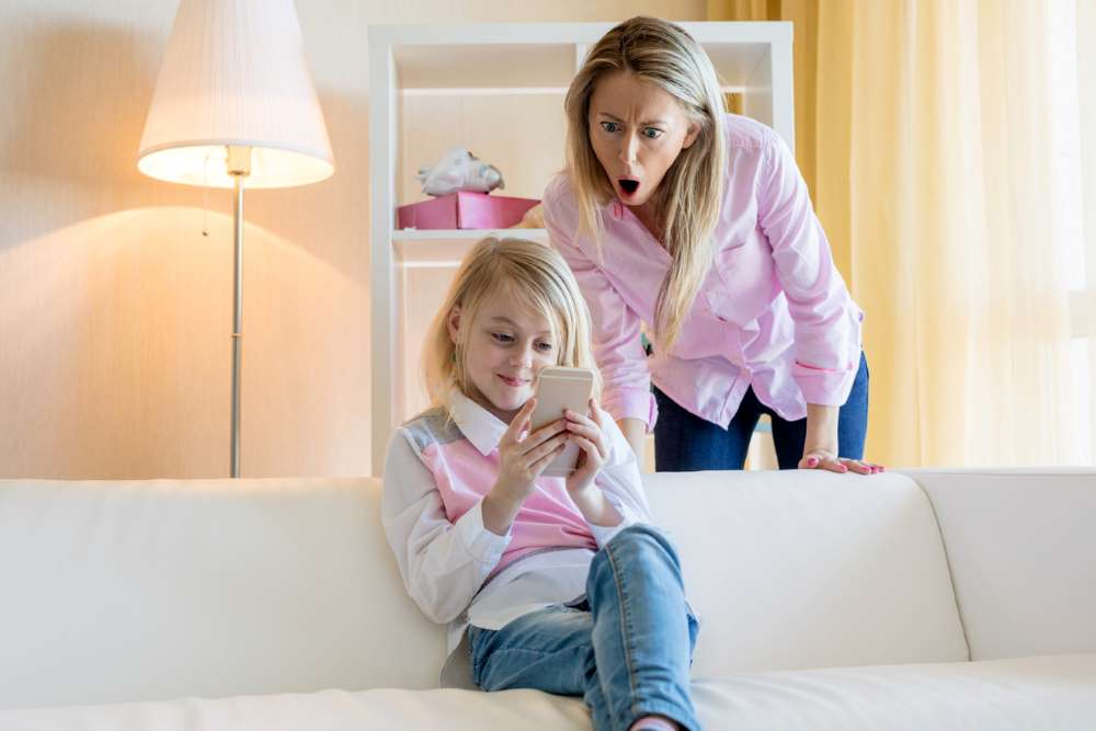 mom looks concerned over daughter's internet use