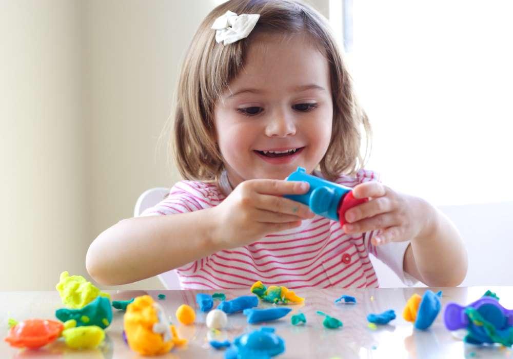 little girl is having fun with playdoh