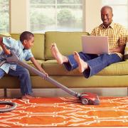 boy vacuming carpet while parents relax
